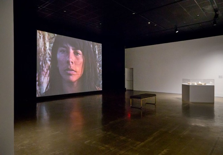 """Installation view of """"Carry Forward"""" at the Kitchener-Waterloo Art Gallery, 2017. (Left) Marjorie Beaucage, """"Speaking to Their Mother"""", 1992, video, 26 minutes. (Right) Maika'i Tubbs, """"Written in Stone"""", 2016, found books, dimensions variable."""